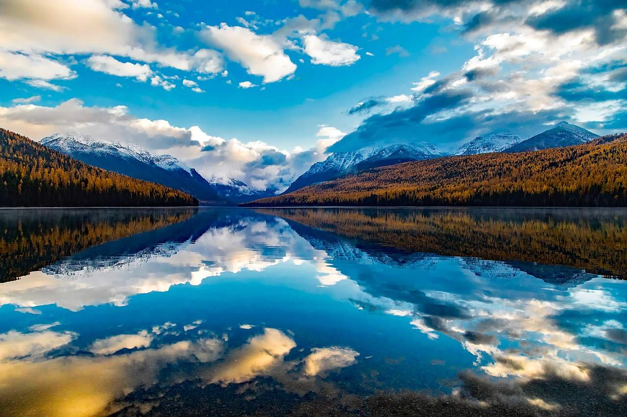 Reflection on Lake Macdonald Montana with mountains, blue sky and clouds reflecting on the lake