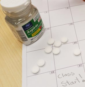 "bottle of aspirin and a calendar with ""class start"" written on it"