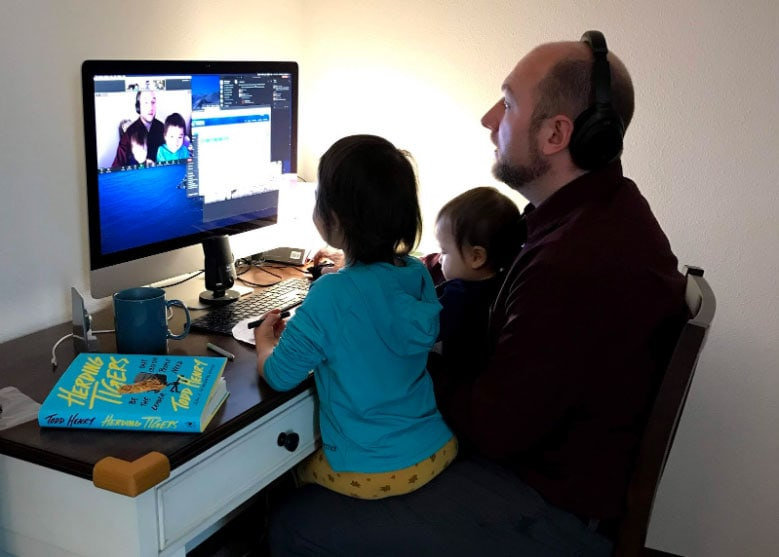 Instructor Sean Holland in his home office conducting a video chat on his computer with his two daughters on his lap.