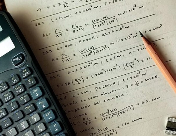 decorative image of a calculator, notebook and equations on paper