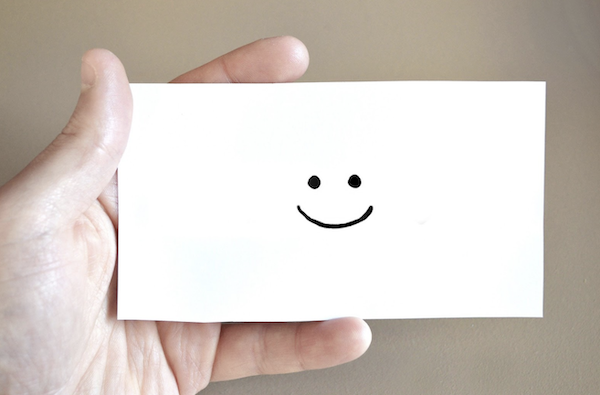 decorative image of a hand holding a card with happy face drawn on the card.