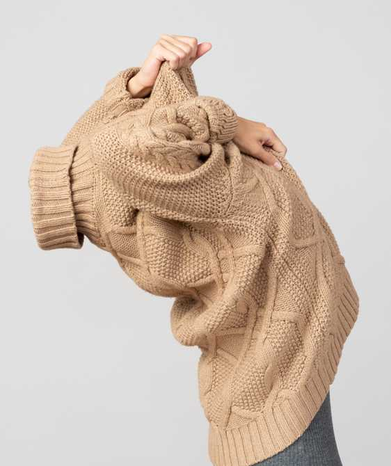 Woman pulling a sweater over her head.
